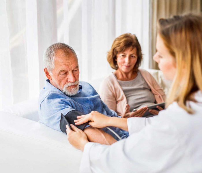 female-doctor-checking-blood-pressure-of-senior-ma-PDN3YZZ.jpg
